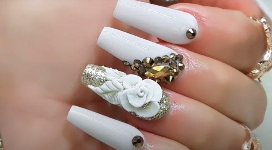 uñas navideñas blancas con piedras y flor blanca toques de dorado